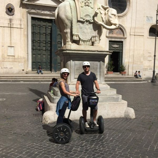A couple on segway posing in front of Bernini`s Elephant near Pantheon in Rome