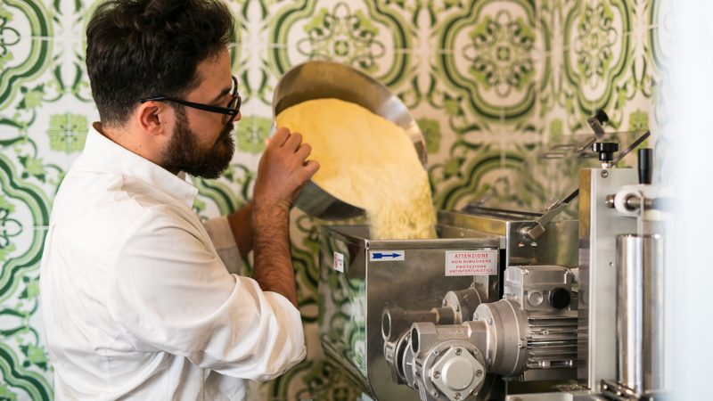 Chef Luciano is throwing the flower to the pasta maker to make his famous home made pasta