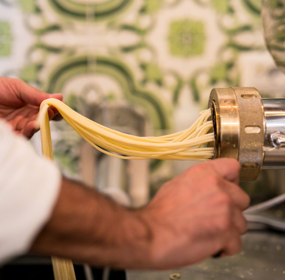 Luciano is taking fresh spaghetti from the pasta maker in his Restaurant in Rome