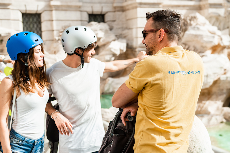 Couple on segway tour relaxing at the Trevi Fountain