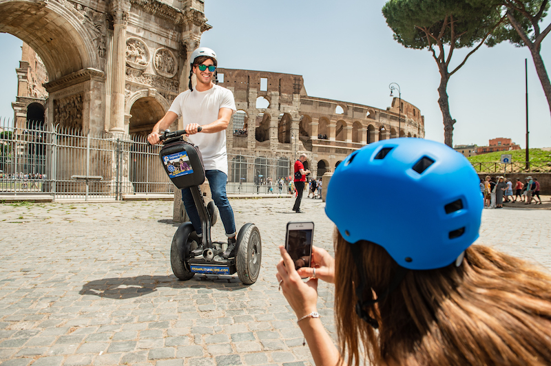 A girl is taking picture of her boyfriend on segway in front of Colosseum