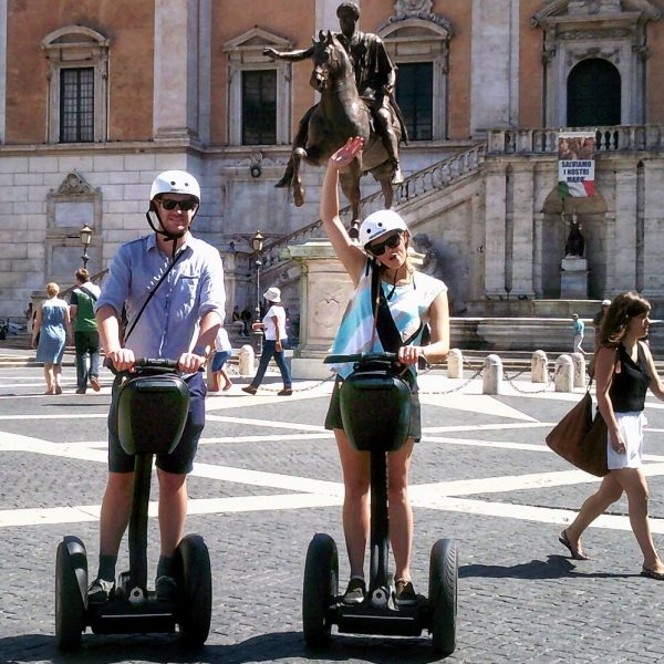 Smiling girl with her boyfriend at the Capitol hill in Rome during their Segway Tour