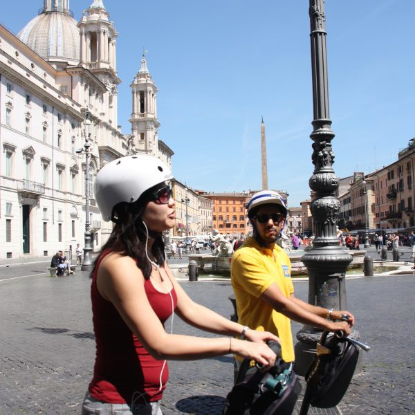 Segway tour guide explaining details of Piazza Navona to a female traveller