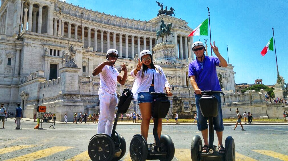 A family on segway posing at the piazza Venezia in front of the monument of Victor Emanuel II