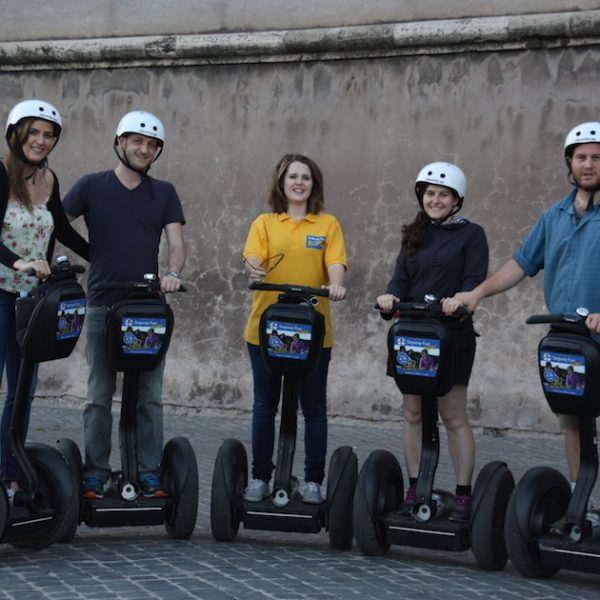 Group of segway riders with the guide in the middle in front of walls of the Vatican