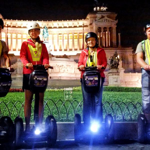 Friends on light up Segways at night in front of monument of Vittorio Emmanuele in Rome