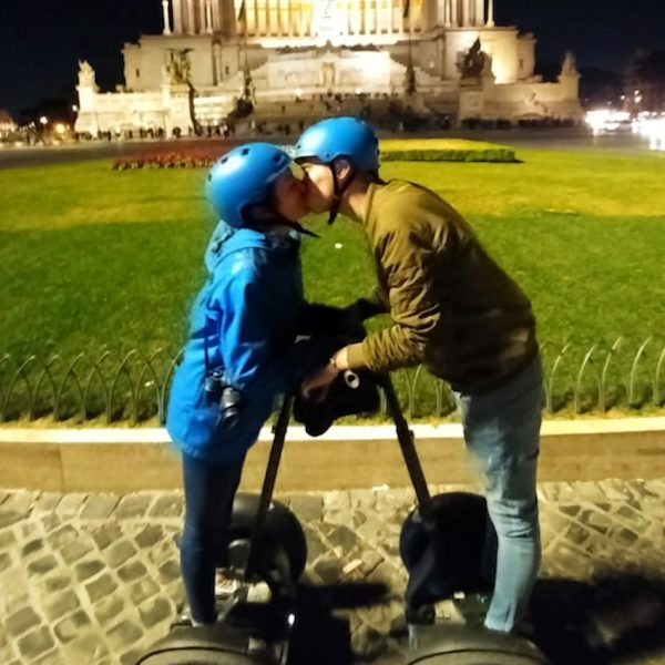 A kiss of a young couple on segway at Piazza Venezia in Rome at Night