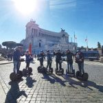 A group of friends on segways at Piazza Venezia are waving to the camera during their segway Grand City tour of Rome