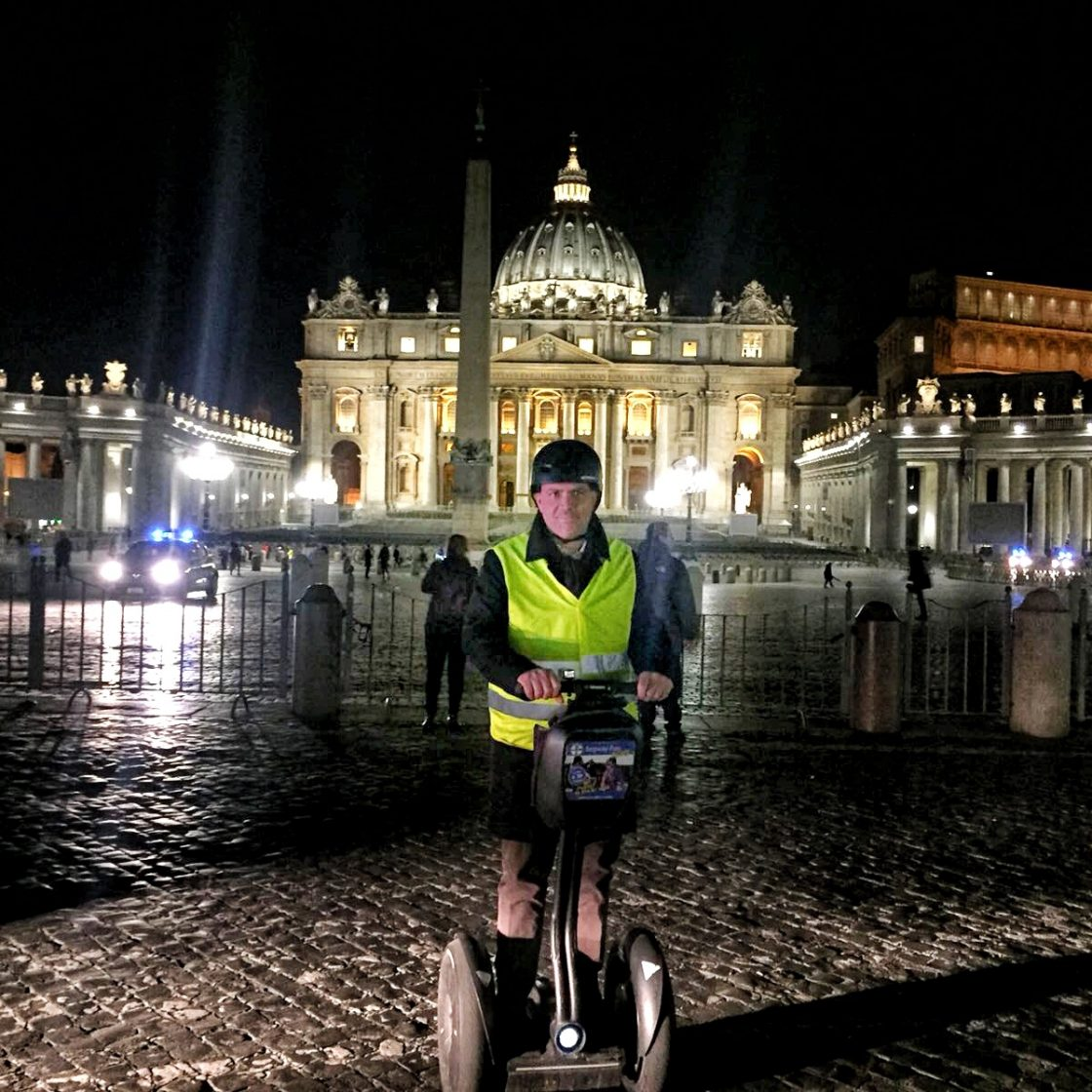A man on segway with a reflective vest in front of Basilica of saint Peter in Rome at Night