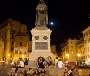 People sitting in front of Statue of Giordano Bruno at Campo de`Fiori in Rome at night