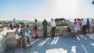 People sitting at the terrace in the Villa Borghese on the top of the Pincio hill and admiring stunning view of Rome