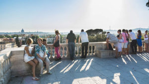 People sitting at the terrace in Villa Borghese on the top of Pincio Hill admiring stunning view of Rome