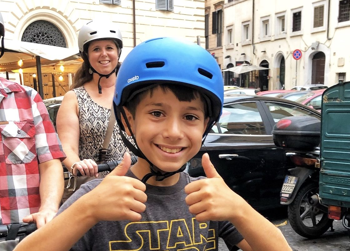 A kid with a helmet with his parents on the segway tour