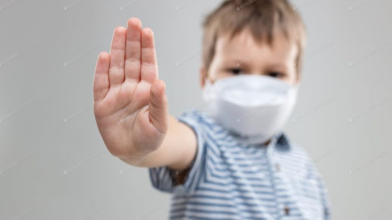 Little boy wearing a mask shows no to the Coronavirus
