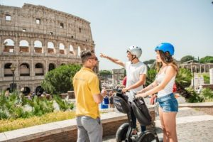 Guide with tourists on segways at colosseum in Rome Italy